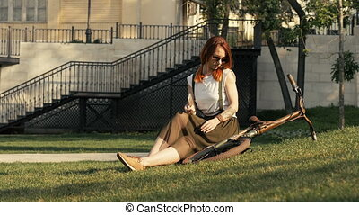 Young redhaired woman cyclist lying on green grass at city...