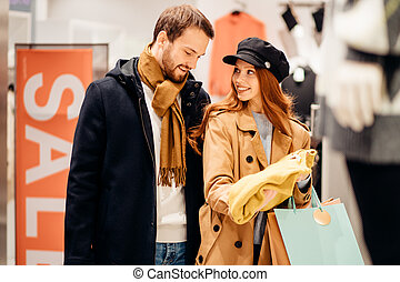 young redhaired woman looking for blouse in shop together with husband