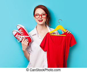 Young redhead designer with dress and gumshoes on blue background