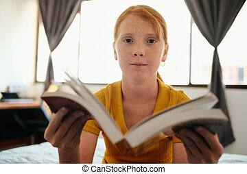 Young Redhead Girl Studying And Showing Book To Camera