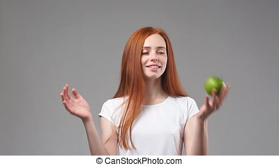 Young redhead girl tosses green Apple. Slow Motion - Young...