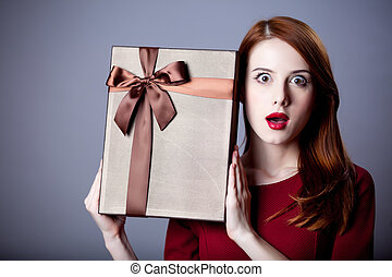 Young redhead girl with gift box