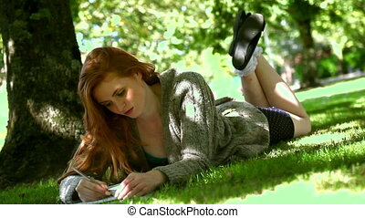 Young redhead lying on lawn while doing assignments on sunny...