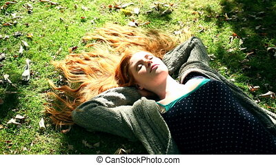 Young redhead relaxing on lawn in bright sunshine