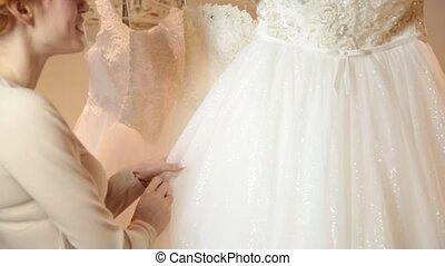 Young redhead woman choosing wedding dress in bridal boutique. bride preparing for wedding
