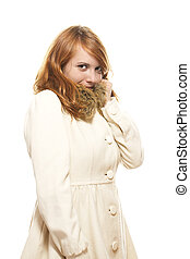 young redhead woman covering her face in fawn winter coat on white background