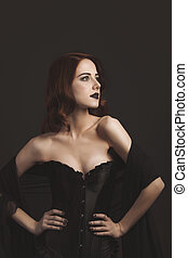 Young redhead woman in black corset