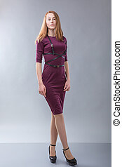 redhead woman in burgundy dress with black belt standing in photostudio on gray background