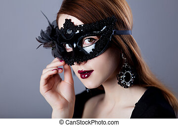 Young redhead woman in carnival mask