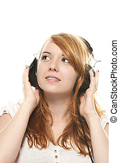 young redhead woman is daydreaming while listening to music with headphones on white background