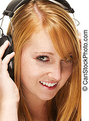 young redhead woman listening to music on white background