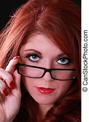 Young redhead woman looking over glasses on nose