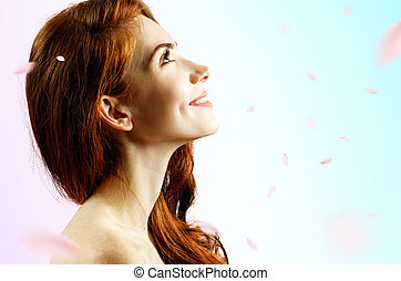 Young redhead woman over fresh blue background with swirl petals.
