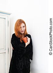 Young redhead woman smiling with orange mug