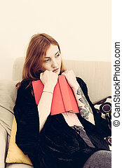 Young redhead woman thoughtful with a book