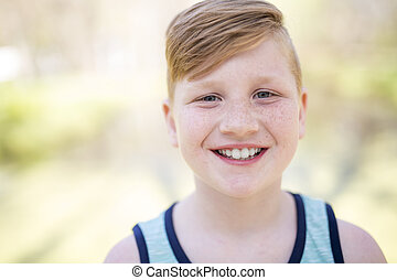 Young redheaded boy playing outside
