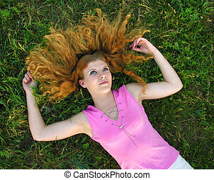 young redheaded woman lying on the grass
