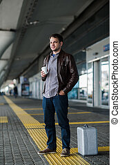 Young regular man standing waiting near the airport with cup of coffee and silver case