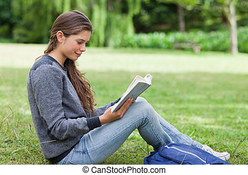 Young relaxed adult reading a book while sitting on the grass