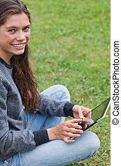 Young relaxed adult sitting down with her tablet computer while looking at the camera