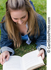 Young relaxed girl lying on the grass while reading a book