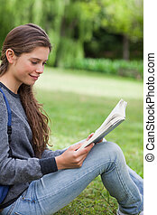 Young relaxed girl reading a book while sitting on the grass in the countryside