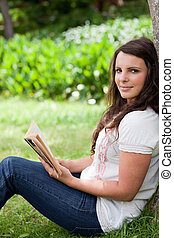 Young relaxed woman looking at the camera while holding a book