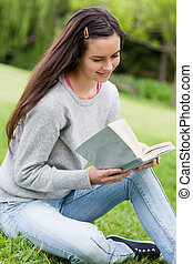 Young relaxed woman sitting down in the countryside while reading a book