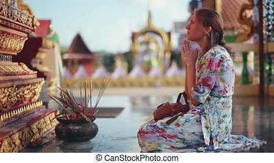 Young religion woman coming in temple prays on the knees at complex Wat Plai Laem. Koh Samui, 1920x1080