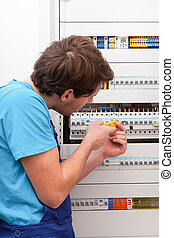 Young repairman checking voltage on switchboard in boiler...
