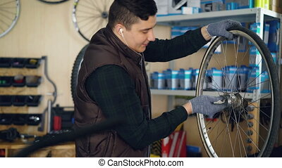 Young repairman is cleansing bicycle wheel inside and...