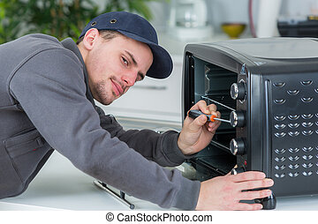 young repairman repairing oven with screwdriver in clients kitchen