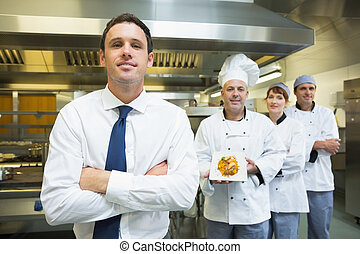 Young restaurant manager posing in front of team of chefs