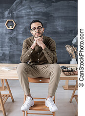 Young restful businessman in casualwear looking at you while sitting on table