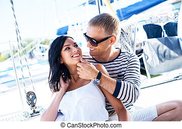 Young, rich and attractive couple on a sailing boat