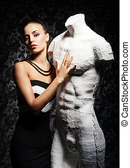 Young, rich and beautiful woman with the mannequin over the ...