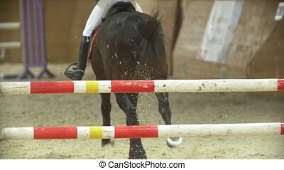 Young rider on black horse galloping at show jumping...