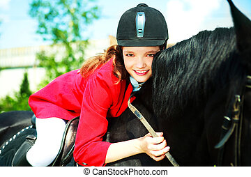 young rider - pretty young woman riding a black horse