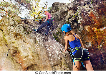 Young rock climber reaching the summit of mountain