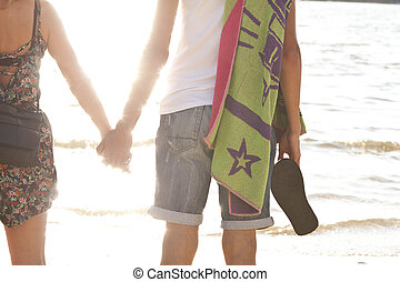 young romantic couple holding hands at sunset