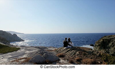 Young romantic couple is enjoying beautiful sunset sitting on the beach and hugging.