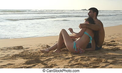 Young romantic couple is enjoying beautiful view sitting on the beach and hugging. A woman and a man sits together in the sand on the seashore, admiring the ocean and landscapes.Slow motion Close Up