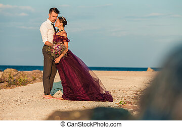 Young romantic couple relaxing on the beach watching the sunset