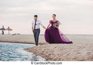 Young romantic couple running on the beach of sea