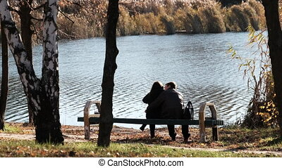 Young Romantic Couple Sitting on a Bench in an Autumn Park ...