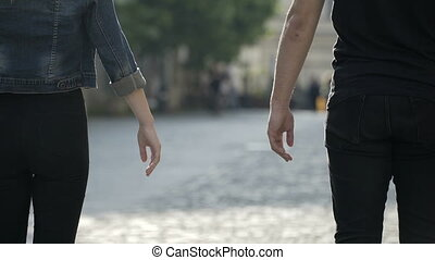 Young romantic couple taking hands and walking together outdoor in the city