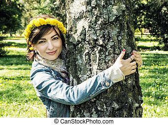 Young romantic woman with wreath of dandelions on the head is hugging the birch in the park