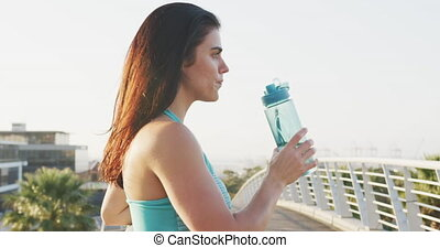 Young runner drinking water after running - Side view close ...