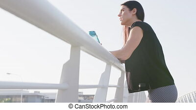 Young runner drinking water after running - Side view of a ...