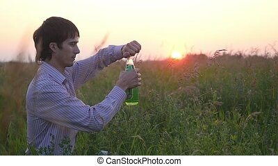 Young runner outside in field resting, drinking lemonade and enjoying drink